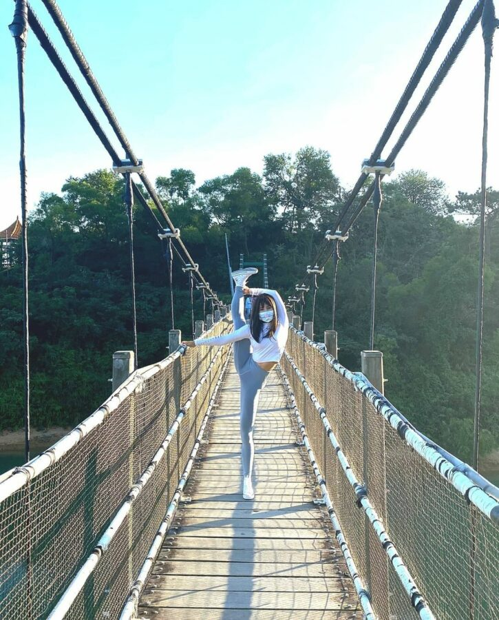 A Person Walking On A Suspension Bridge  Description Automatically Generated With Low Confidence