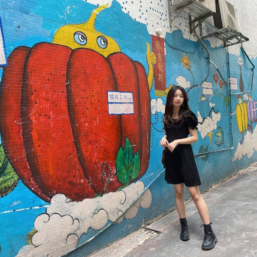 A Person Standing In Front Of A Wall With Graffiti  Description Automatically Generated With Medium Confidence