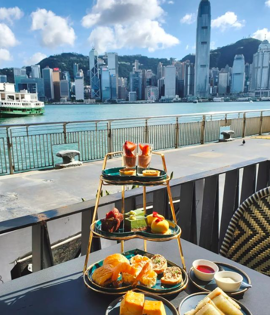 A Table With Food On It By A Body Of Water With A City In The Background  Description Automatically Generated With Medium Confidence